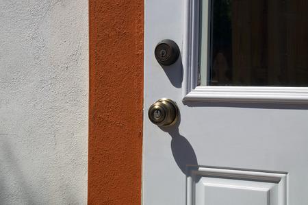 Detail of door with door knob and deadbolt on typical florida home. 版權商用圖片