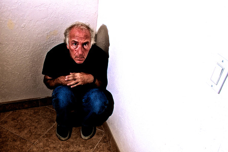 looking at viewer: An older white man is crouched down in a corner looking up fearfully at viewer.