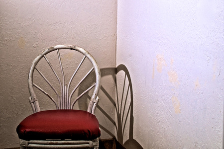 An old white bamboo chair with red vinyl seat in corner of empty room. Stock fotó