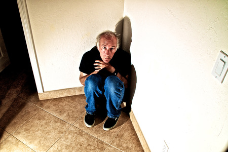 Looking down on an older man hunched down the the corner of an empty room, looking up terrified. photo