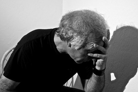 holding the head: Portrait of a distressed older white man holding head sitting in corner of white room.