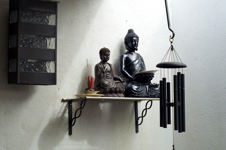 wind chime: Two Buddha statues on shelf from different asian traditions with incense against stucco wall with windchime.