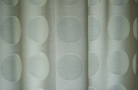 Close up of polka dotted curtains with folds in the fabric.