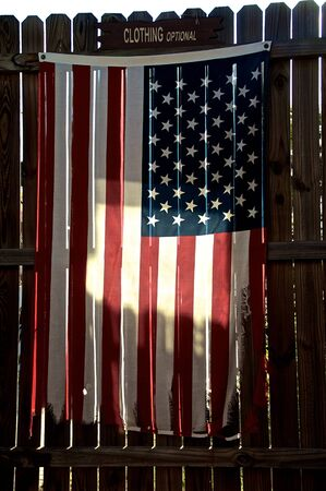 optional: An old tattered and worn american flag is hanging on a stockade fence, backlit by morning sun with clothing optional sign above. Stock Photo