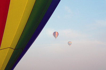 high up: Two hot air balloons can be seen high up in the sky and partially obscured by the fog in the air The side of another balloon fills the side of the image up close. Stock Photo