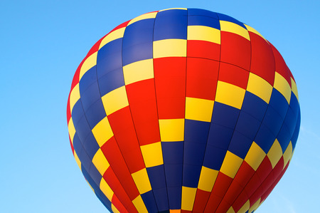 A red blue and yellow hot air balloon showing just the top against blue sky. Stok Fotoğraf