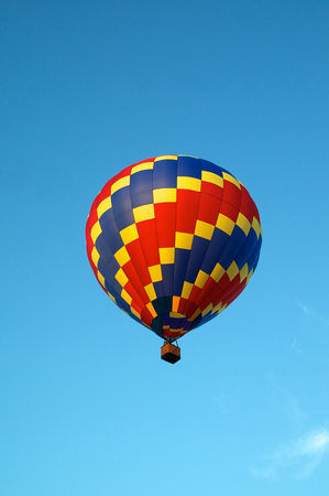 Looking up at a red blue and yellow hot air balloon as it soars and flies in the clear blue sky. Stok Fotoğraf