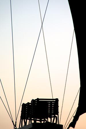 朝の空に対してシルエットにバーナー談合と熱気球の曲線を示します。