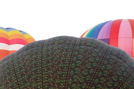 washed out: Tops of three colorful  hot air balloons against a washed out morning sky.