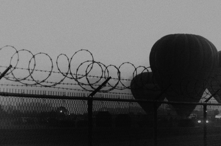 barbed wire fence: Outside early morning fog and three hot air balloons can be seen in the distance behind a barbed wire fence. Finished in black and white and film grain to make the image more timeless.