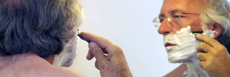 shaving cream: A man with eyeglasses has shaving cream on his face and looking in the mirror is beginning to shave. Stock Photo