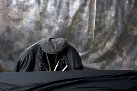 tweed: A leather motorcycle jacket hangs on the back of a chair with a tweed cap sitting on top behind a black covered table.