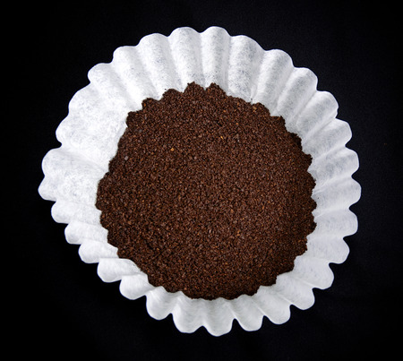 resembling: Looking down on a coffee filter with dry grounds on black resembling a flower.