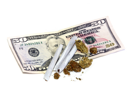 50 dollar bill: A 50 dollar US bill is shown under a cluster of marijuana pot buds and three joints, over white. Stock Photo