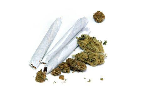 marihuana: Un grupo de brotes de marihuana y tres articulaciones de cerca m�s de blanco. Foto de archivo