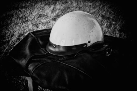 gritty: A grainy gritty image of a battered white motorcycle helmet resting on a black leather biker jacket, finished in black and white.