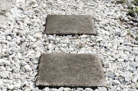 stepping: Two square stepping stones at an angle surrounded by white crushed marble stone. Stock Photo