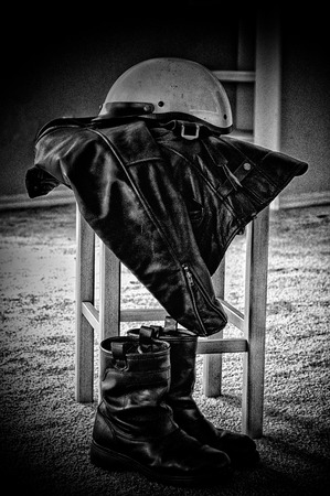 gritty: A grainy gritty image of a battered white motorcycle helmet resting on a black leather biker jacket,  and riding boots on the floor, finished in black and white. Stock Photo