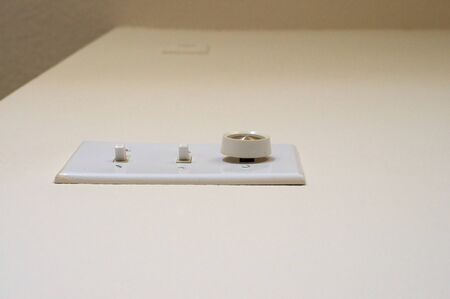 dimmer: Looking up from the floor at a bank of light switches, two toggle switches, and one dimmer knob on empty light colored wall.
