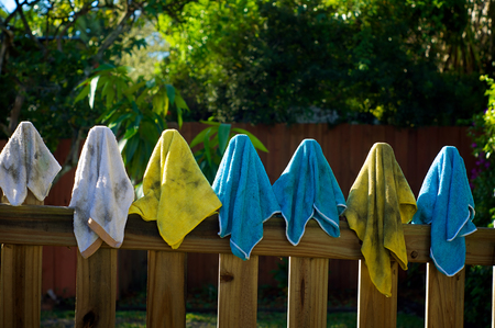 terrycloth: A collection of colorful dirty microfiber  and  terrycloth rags or cleaning cloths on fence posts drying in the sun.
