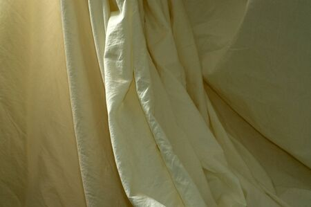 A neutral off white muslin backdrop is draped with vertical theatrical folds.