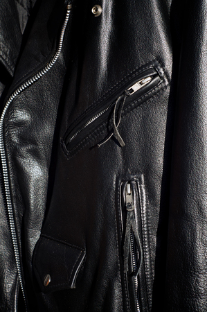 classic contrast: A worn classic black leather motorcycle jacket in sunshine showing zippered pockets and change pocket with flap.