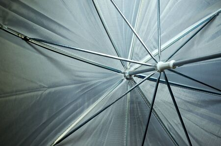 Looking at the inside of a photographers white umbrella, showing the framework.