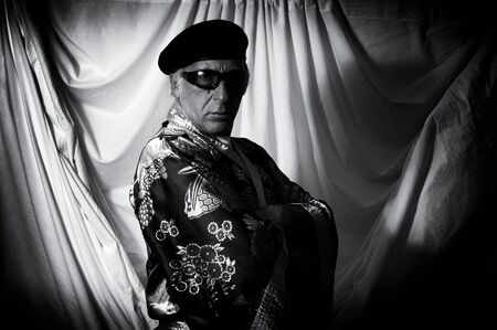 An eccentric mystic in kimono, beret and sunglasses looking at the viewer with body turned away and arms folded in this high contrast black and white image.