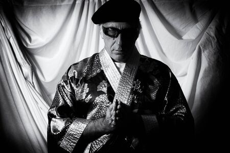 looking at viewer: An eccentric holy man in kimono, beret and sunglasses looking at the viewer with hands together in prayer in this high contrast black and white image.