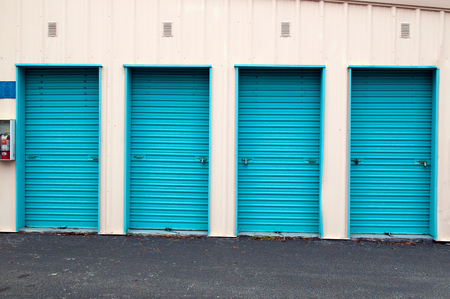 storage units: set of four metal roll up doors of storage units, closed and locked.