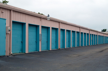 locked door: A storage unit building showing long row of doors with diminishing perspective.