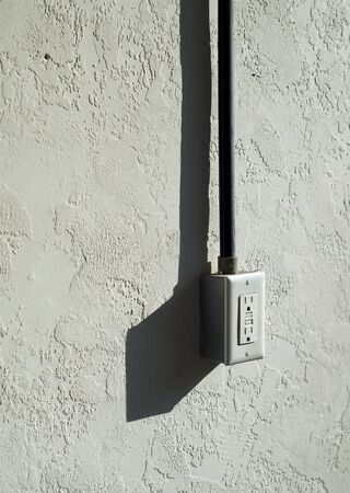 A stuccoed wall with electrical outlet mounted outdoors.