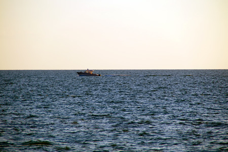 gulf of mexico: A boat is moving across the water on the gulf of mexico in bonita springs, florida as the sun sets. Stock Photo