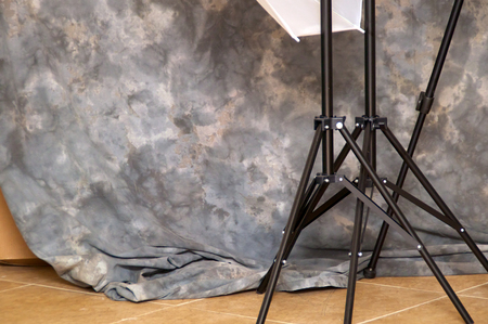 behind the scenes: View behind the scenes of mottled background and light stand tripod legs at photo studio.