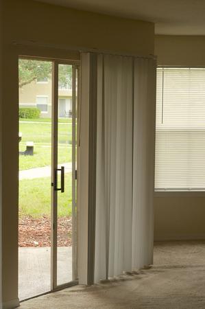 sliding door: Looking towards an open sliding door in empty apartment with vertical and horizontal blinds.