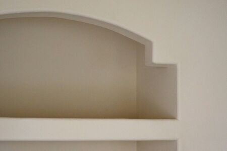 cubby: View of an empty built in shelf with arch in empty room.