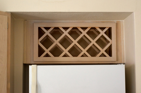 built in: View of an empty built in wine rack above refrigerator in apartment.