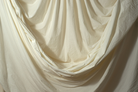 backdrop: Off white draped muslin backdrop with unique folds and drapes. Stock Photo