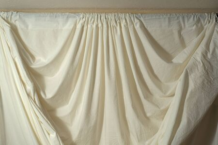 bunched: Off white draped muslin backdrop with unique folds and drapes, showing top where it is bunched on rods. Stock Photo