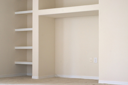 cubby: View of a portion of a wall with built in book shelves and cubby in modern apartment.