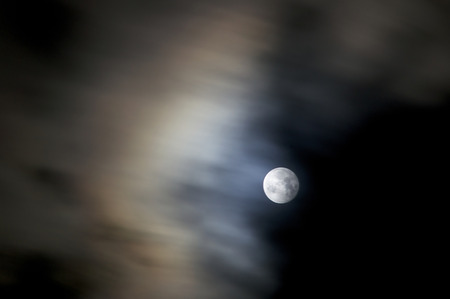 A 8 second exposure of a full bright moon on an autumn night with fast moving clouds creating blur.