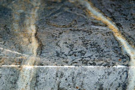 soapstone: Close up angled view of the edge of a slab of unfinished black soapstone, showing veins and scratches. Stock Photo