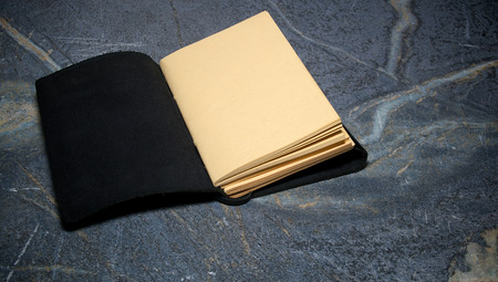 soapstone: A black leather bound book is open to the first page that is blank on soapstone table top.