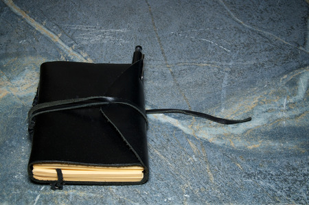 A black leather writer notebook or artist sketchbook on marbled surface. Book is closed with leather cord, pencil is tucked into flap. Stock Photo
