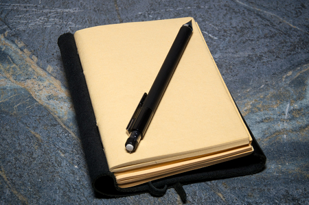 soapstone: A black leather bound writing journal or artist sketchbook is open to blank page with mechanical pencil resting on page on soapstone surface.