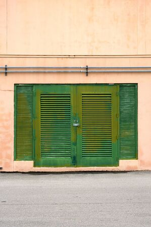 padlocked: A set of old green weathered doors, padlocked and looking like shutters on exterior wall with shutters. Stock Photo