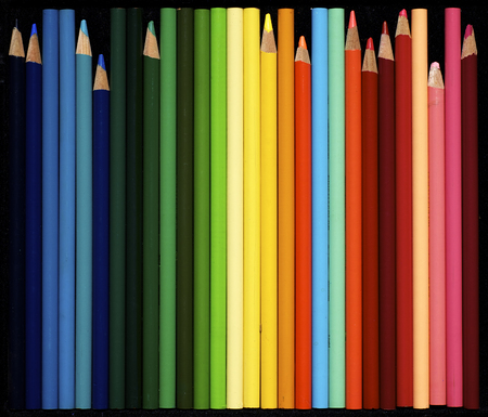 Numerous colored pencils , new and used lined up with a black background. Stock Photo