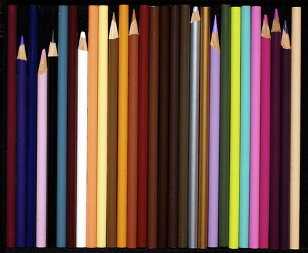lined up: An assortment of various colored pencils, lined up in a row on black.