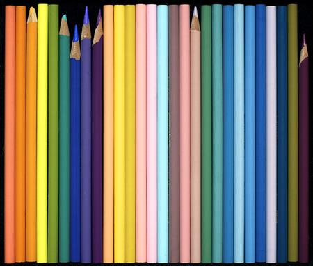 Een groep van nieuwe en gebruikte kleurpotloden op een zwarte achtergrond. Stockfoto