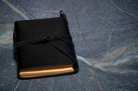 soapstone: A black leather writer notebook or artist sketchbook on marbled surface. Book is closed with leather cord, pencil is tucked into flap. Stock Photo